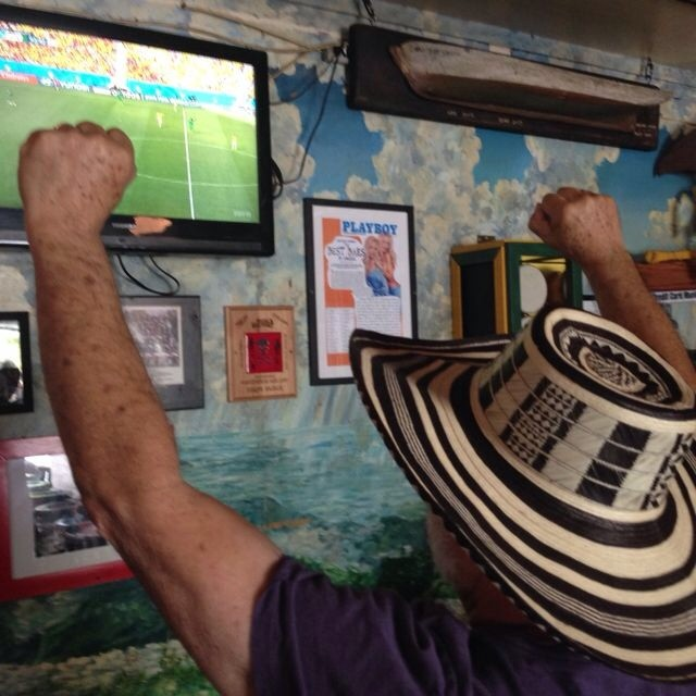 Sporting the hat gifted him by Ernesto and Clara, John cheers the Colombian squad to victory at The Green Parrot Bar in Key West!