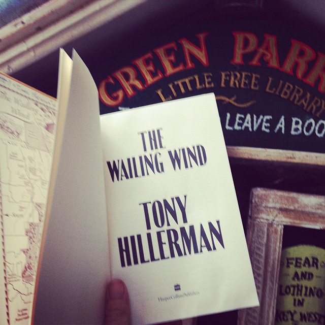 Curating the Green Parrot Little Free Library on rainy Sunday morning<br /> with more rain on the way.<br /> I spy a new volume, no dust jacket but the author's name on the spine  catches my eye, Tony Hillerman.<br /> Perfect day to spend with The Tribal Police in the land of the Navajo.<br /> Thanks, Green Parrot Little Free Library!<br /> As a footnote, on the Other Books<br /> by the Author page, the previous owner had checked off nearly all of Hillerman's previous books as well as some marginalia on how often a certain phrase appear in this particular novel.<br /> That's another reason I love used books, and our little library. While a brand new book communicates with it's first-reader alone, a used book has the possibility of granting us, the current owner, a sort of legacy from past owners as well, be it a note on the flyleaf, a coffee stain, or a greyhound bus ticket used as a bookmark.#greenparrotbar #tonyhillerman #joeleaphorn #marginalia #littlefreelibrary&nbsp;