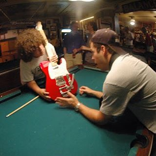 Back in 2007, my son Dan was into guitars, specifically building guitars. With parts gathered from many sources on eBay, he built a candy-apple red Muddy Waters Telecaster, working mostly on the kitchen table. Albert Castiglia and Dan were friends,  so when Dan told  Albert about the home-made Tele, Albert demanded to see it, then asked to play it. He must have  liked it, so much so that  he played the whole 90 minute soundcheck with it.That's Dan (with the Buddy Miles fro) and Albert checking out one of the custom features, namely the chrome Gretch Bigsby whammy bar, after soundcheck. That's my older son Nick, on the right behind the pool table talking to Richard Talmedge from The Restaurant Store. Albert's here the rest of the weekend including Sunday soundcheck.#greenparrotbar #greenparrotsoundcheck #albertcastiglia #muddywaters #muddywaterstele #fenderguitars #telecaster #bigsby #savefamilyphotos
